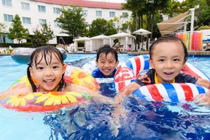 プールで浮き輪で遊ぶ男の子と女の子の写真素材 [FYI01567738]