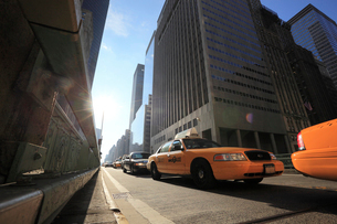 マンハッタン摩天楼と太陽とタクシーの写真素材 [FYI01567746]