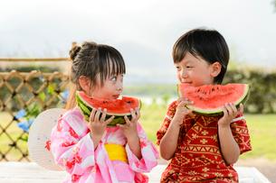 スイカを食べる甚平を着た男の子と浴衣の女の子の写真素材 [FYI01567829]