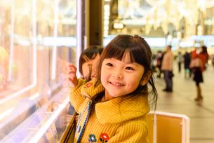 クリスマスで飾ったショウウインドーを見る女の子の写真素材 [FYI01567840]