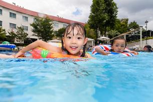 プールで浮き輪で遊ぶ女の子と男の子の写真素材 [FYI01567886]