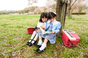 桜の木の下に座る女の子の写真素材 [FYI01567911]