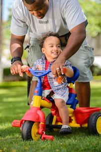 公園で三輪車に乗る子どもと父親の写真素材 [FYI01567945]