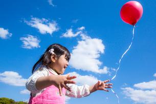 風船を飛ばす女の子の写真素材 [FYI01567966]