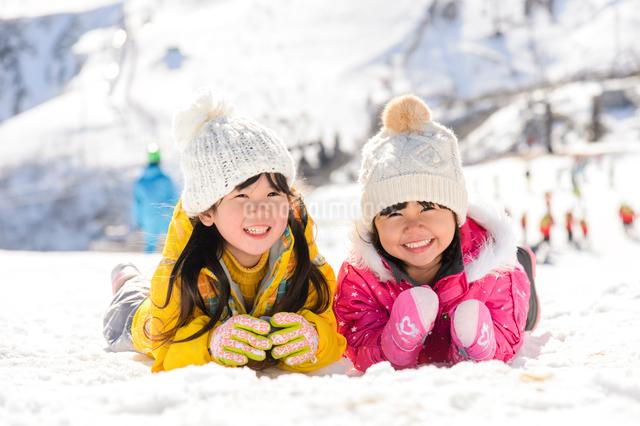 雪上で腹ばいになっている子供の写真素材 [FYI01568030]