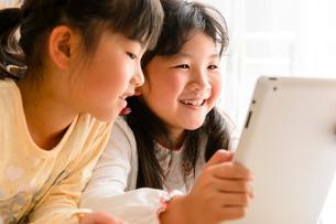 子供部屋でタブレットで遊ぶ女の子の写真素材 [FYI01568049]