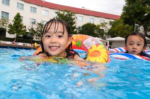 プールで浮き輪で遊ぶ女の子と男の子の写真素材 [FYI01568107]