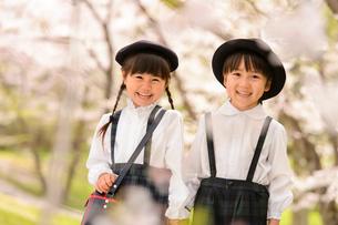 桜の木の前に立つ女の子と男の子の写真素材 [FYI01568159]