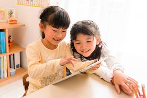 子供部屋でタブレットで遊ぶ女の子の写真素材 [FYI01568252]