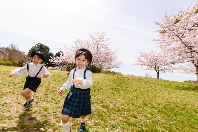 公園をかけっこする女の子と男の子の写真素材 [FYI01568269]