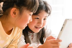 子供部屋でタブレットで遊ぶ女の子の写真素材 [FYI01568271]