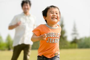公園で走る父子の写真素材 [FYI01568273]