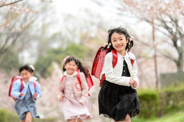 ランドセルを背負ってかけっこする女の子の写真素材 [FYI01568278]
