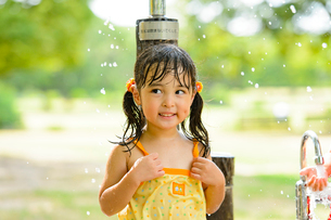 公園の水飲み場で水遊びする女の子の写真素材 [FYI01568318]