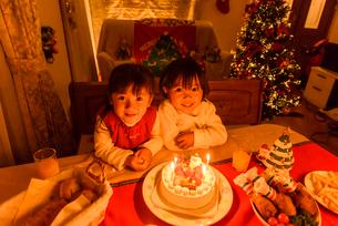 クリスマスパーテイーにご馳走が並ぶテーブルの前に座る女の子の写真素材 [FYI01568337]