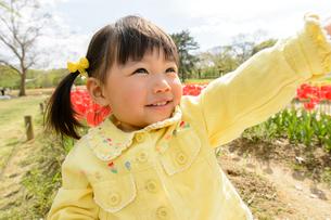 春の公園でチューリップ畑で遊ぶ女の子の写真素材 [FYI01568461]