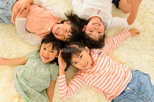 リビングの床で寝そべる女の子の写真素材 [FYI01568497]