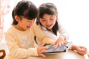 子供部屋でタブレットで遊ぶ女の子の写真素材 [FYI01568498]