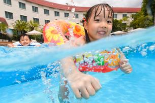 プールで浮き輪で遊ぶ女の子と男の子の写真素材 [FYI01568537]