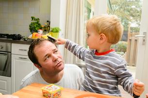 ブラシでお父さんの髪を触る男の子の写真素材 [FYI01568606]