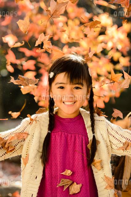 落ち葉を集めてまき散らす女の子の写真素材 [FYI01568615]