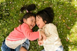 芝生の上に寝転がる子どもの写真素材 [FYI01568616]