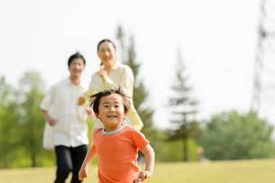 公園で走る親子の写真素材 [FYI01568639]