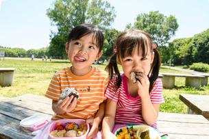 公演のベンチでおにぎりを食べる女の子の写真素材 [FYI01568641]
