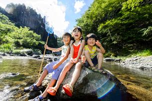 夏の川で石の上に座って遊ぶ女の子と男の子の写真素材 [FYI01568644]