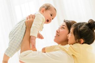 赤ちゃんを抱っこするお母さんとお姉ちゃんの写真素材 [FYI01568663]