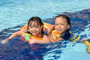 プールで浮き輪で遊ぶ女の子と男の子の写真素材 [FYI01568675]