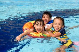 プールで浮き輪で遊ぶ女の子と男の子の写真素材 [FYI01568679]