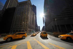 ミッドタウン高層ビル群と太陽とタクシーの写真素材 [FYI01568705]
