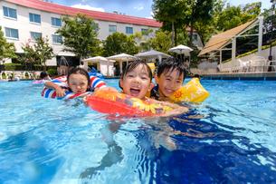 プールで浮き輪で遊ぶ男の子と女の子の写真素材 [FYI01568718]