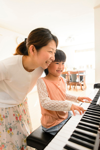 ピアノを弾く女の子と見守るお母さんの写真素材 [FYI01568730]