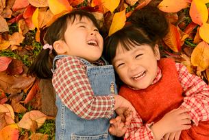 落ち葉の上に寝転がる女の子の写真素材 [FYI01568736]