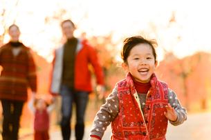 秋の公園を走る子どもと家族の写真素材 [FYI01568781]