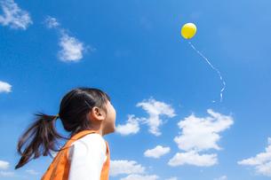 風船を飛ばす女の子の写真素材 [FYI01568875]