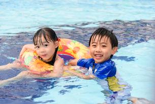 プールで浮き輪で遊ぶ女の子と男の子の写真素材 [FYI01568876]