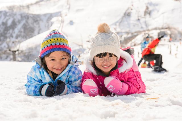 雪上で腹ばいになっている子供の写真素材 [FYI01568930]