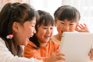 子供部屋でタブレットで遊ぶ女の子の写真素材 [FYI01569003]