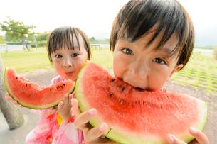 スイカを食べる甚平を着た男の子と浴衣の女の子の写真素材 [FYI01569058]