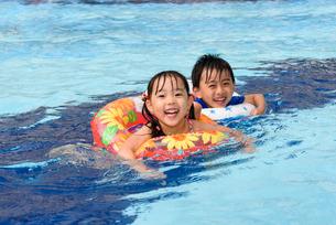 プールで浮き輪で遊ぶ女の子と男の子の写真素材 [FYI01569092]