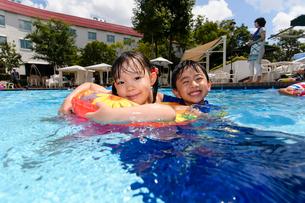 プールで浮き輪で遊ぶ男の子と女の子の写真素材 [FYI01569099]