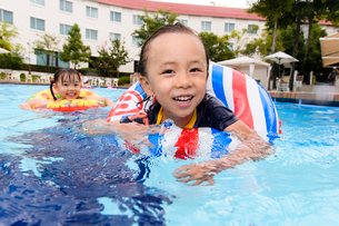 プールで浮き輪で遊ぶ男の子と女の子の写真素材 [FYI01569121]