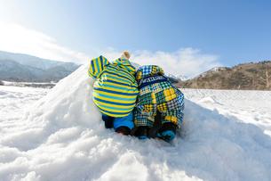 雪山でカマクラに入る子どもの写真素材 [FYI01569244]