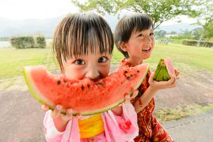 スイカを食べる甚平を着た男の子と浴衣の女の子の写真素材 [FYI01569249]