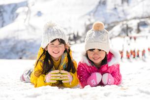 雪上で腹ばいになっている子供の写真素材 [FYI01569254]