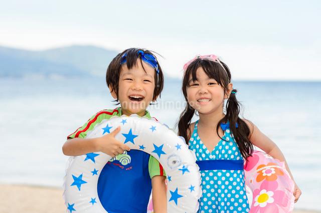 夏の海で浮き輪を持って並ぶ女の子と男の子の写真素材 [FYI01569279]