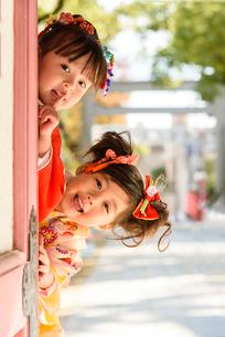 神社の片隅から覗き込む晴れ着を着た女の子の写真素材 [FYI01569284]